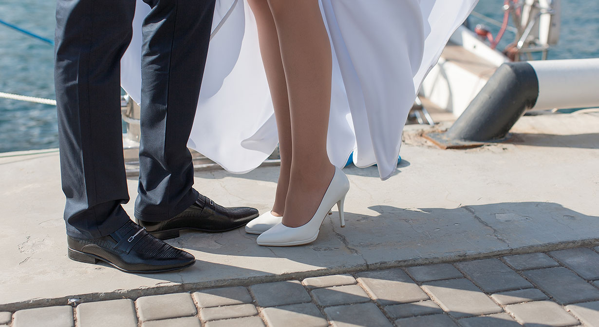 legs of bride and groom at water